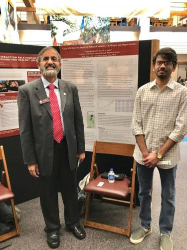 """Dr. Almas and his graduate student, Raghu, presenting their research poster titled """"Egypt's Reliance on Imported Wheat: Concerns, Challenges, and Opportunities"""" at the 14th Annual Faculty Research Poster Session and Research Fair held at the West Texas A&M University"""